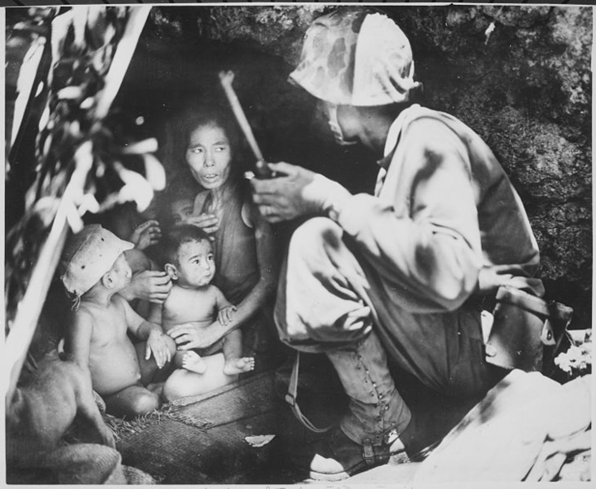 World War Two: A Marine coaxes a mother, four children and a dog, from a cave.