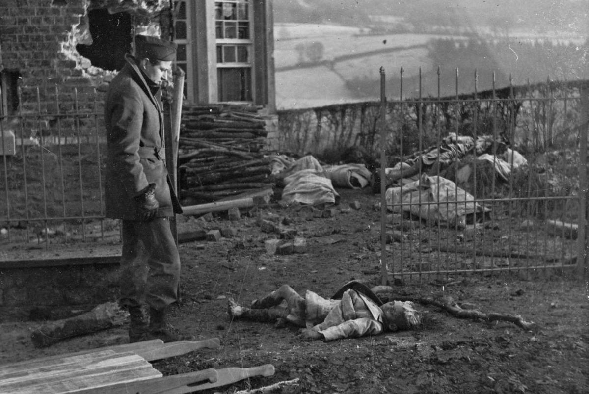 A war correspondent stares in disbelief at the body of a little girl killed by the Germans in Stavelot, Belgium. She was one of a 111 civilians massacred by the Nazis.