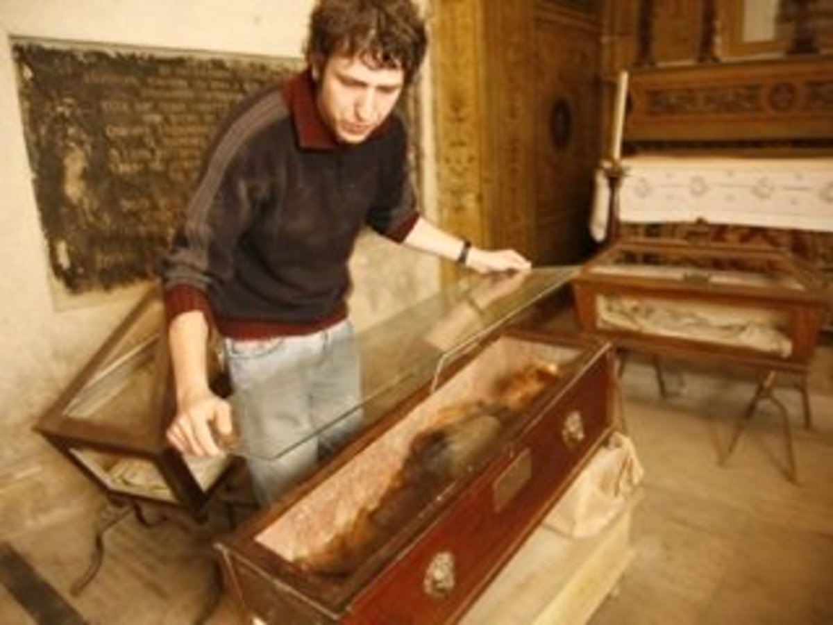 A caretaker at the catacombs overlays a second sheet of glass over Rosalia's coffin for added protection.