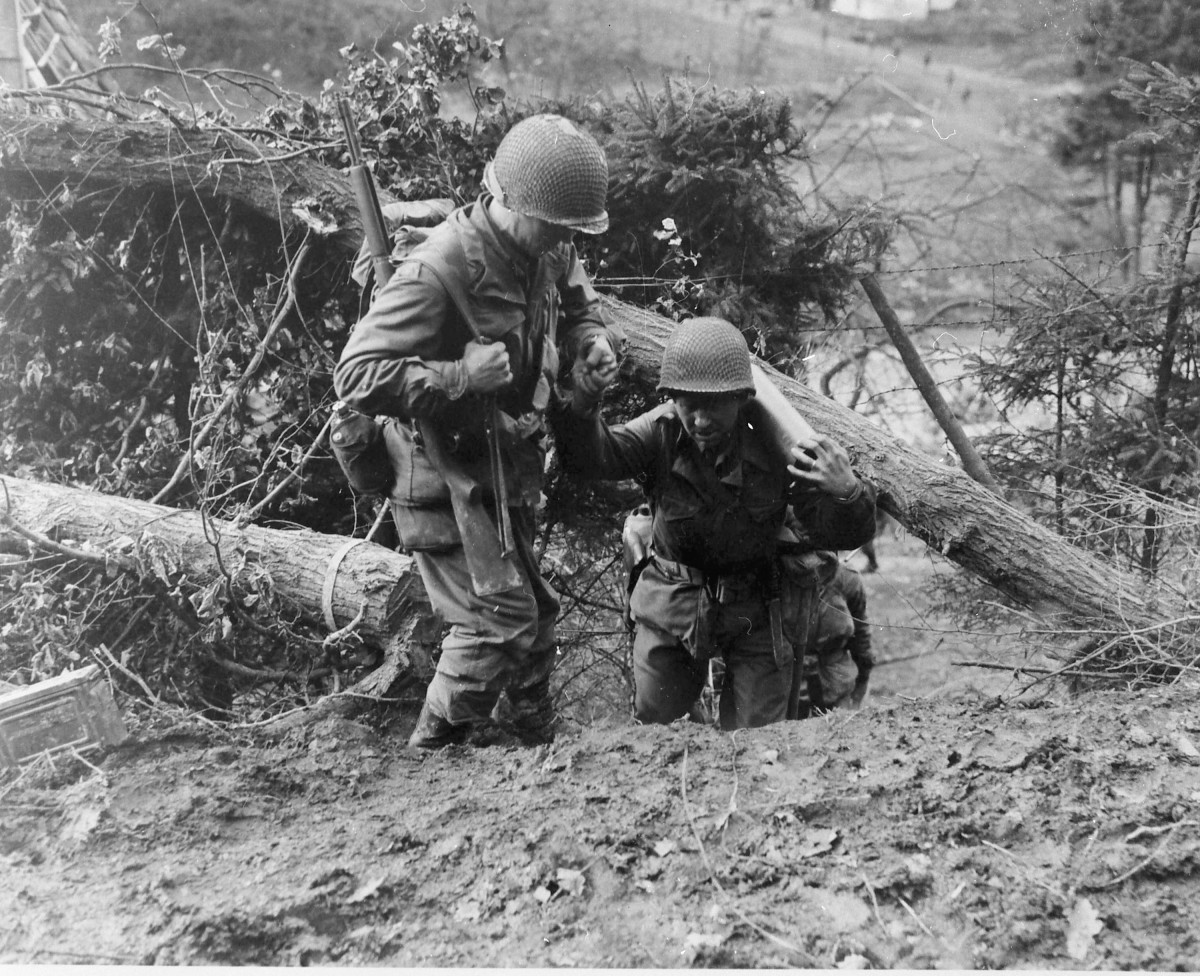 Men of the 4th ID trudge up a steep hill in the Huertgen.
