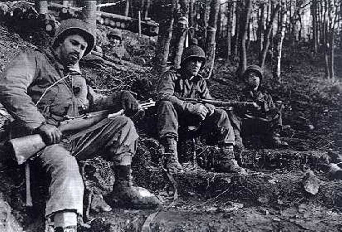 One look says it all: Grim GIs from the 8th Infantry Regiment of the 4th ID taking a break in the Huertgen. They appear to be wearing overshoes, which helped a lot in keeping their feet warm and dry. Those would become in short supply by winter.