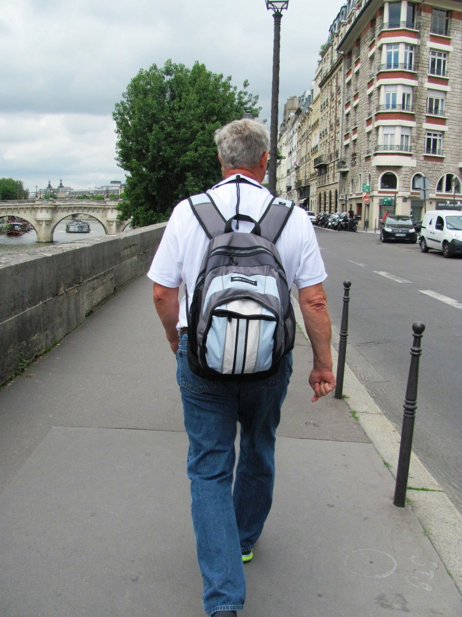 My dad walks alongside the River Seine in Paris near the location of the French National Police on the  Ile de la Cite.