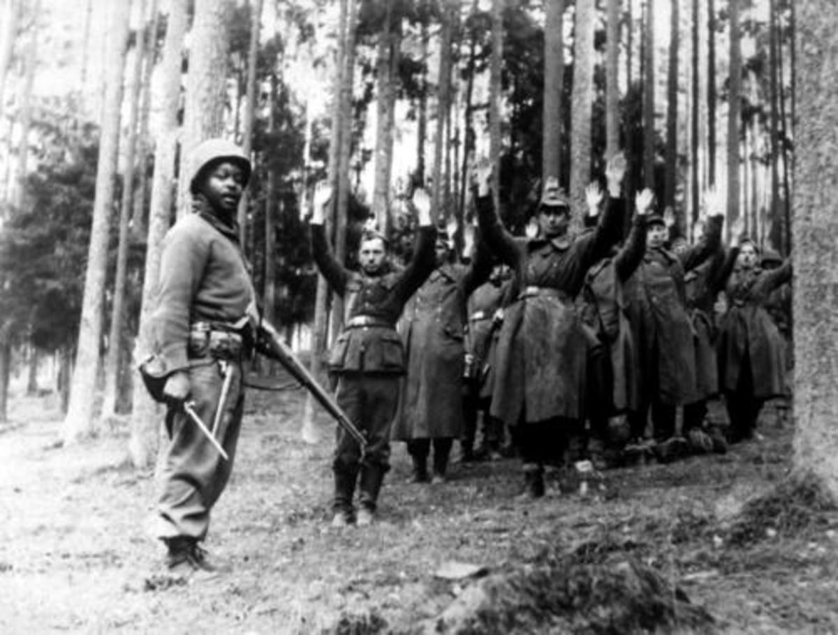 The war is over for you: A soldier assigned to the 14th Armored rounds up German prisoners.