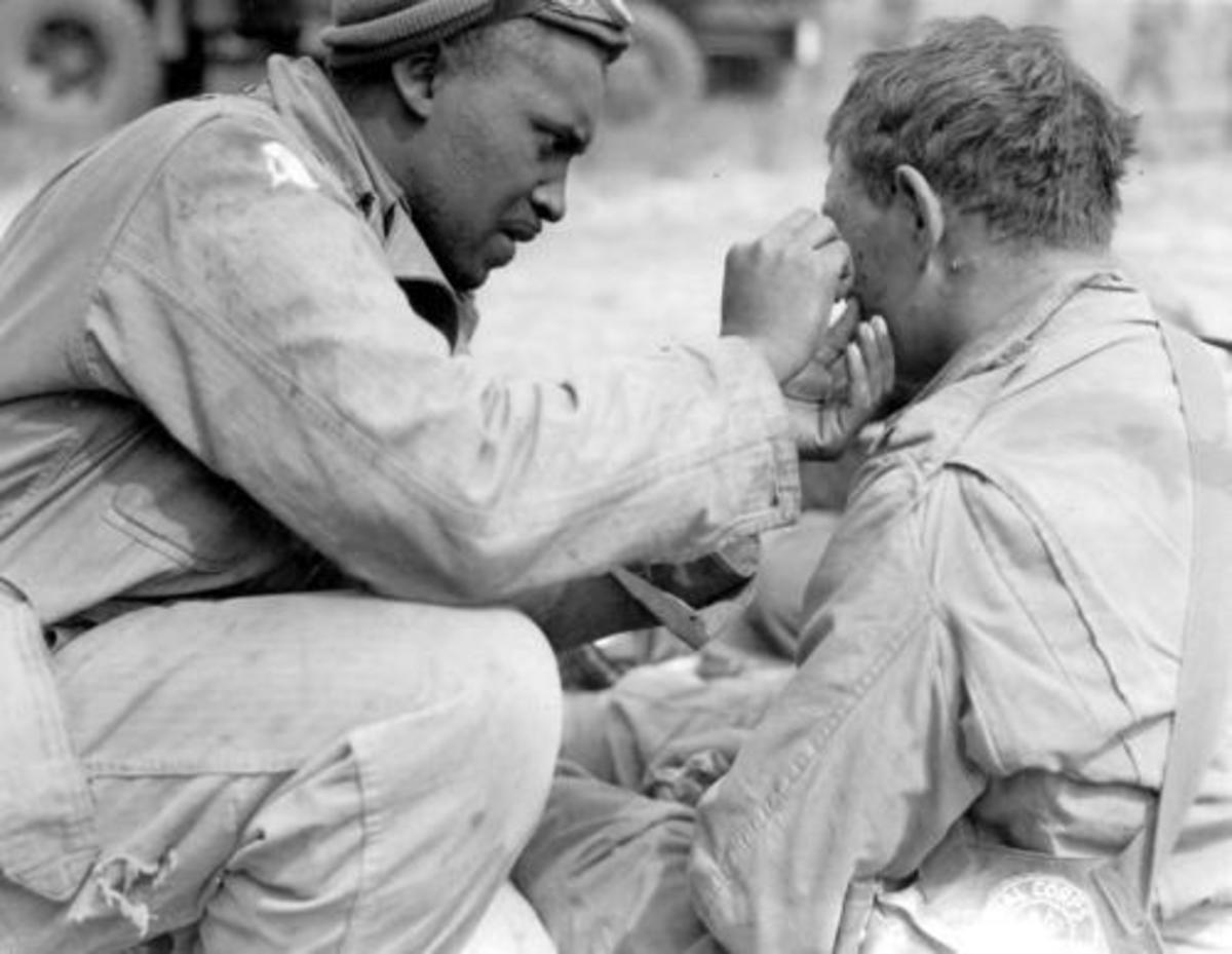We're all Americans - Black soldier helping white comrade on the Normandy beaches.