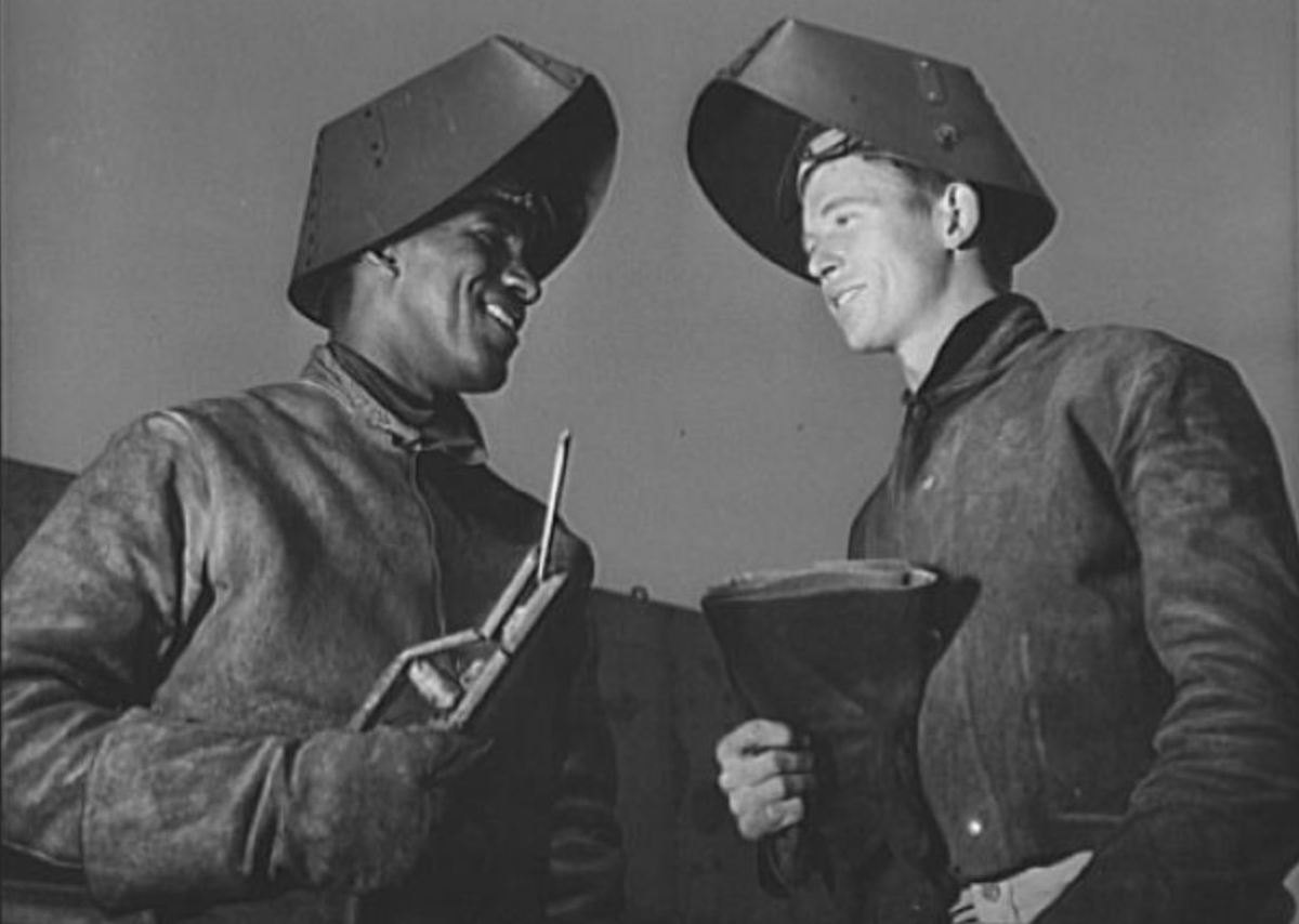 "Original 1942 caption: Jesse Kermit Lucas, experienced Negro welder at the California Shipbuilding Corporation's yards, is shown instructing his white welder apprentice, Rodney Gail Chesney, as the two work on the ""Booker T. Washington"""