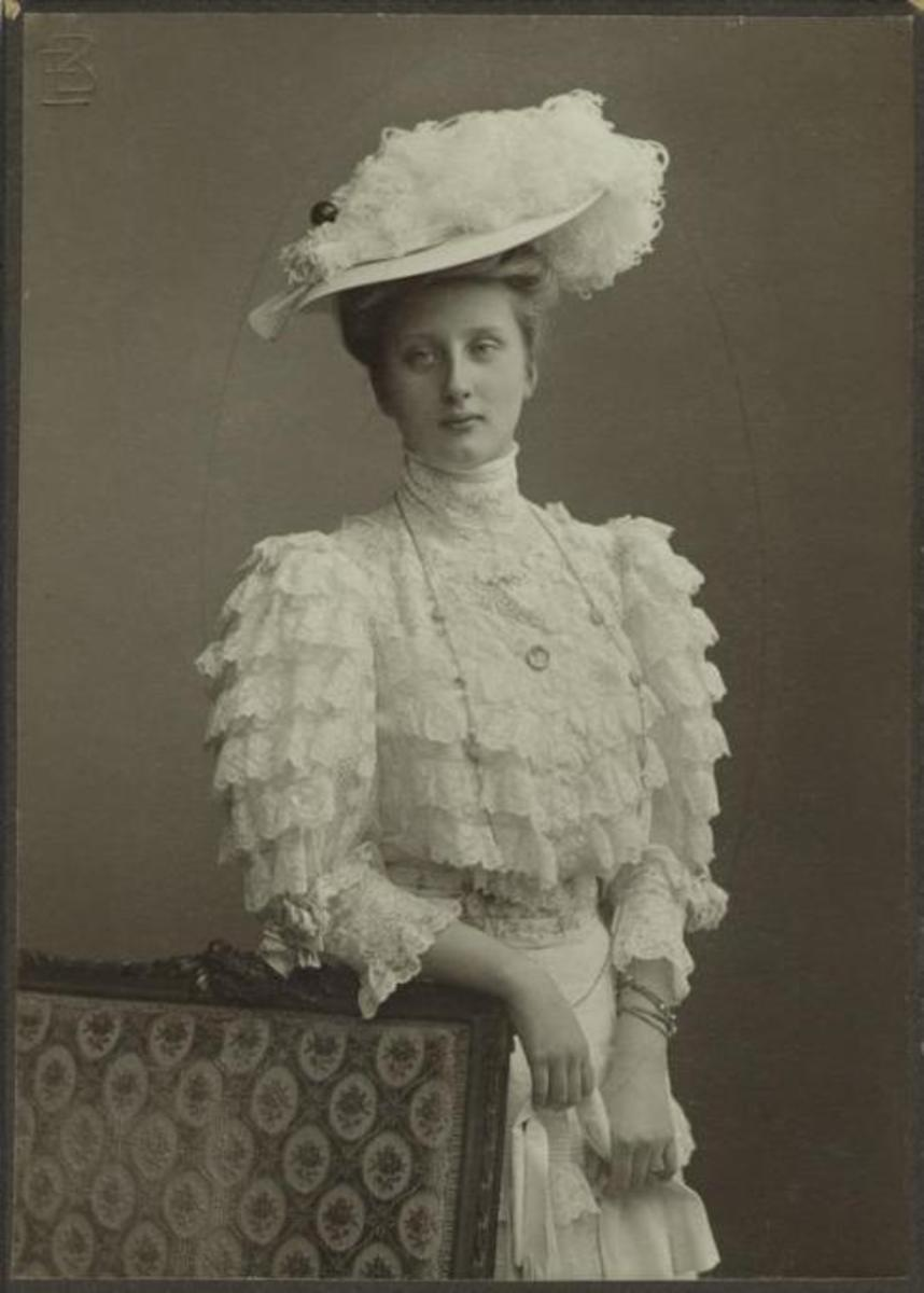 Upper class woman of the late 1800s wearing a white ruffle blouse.