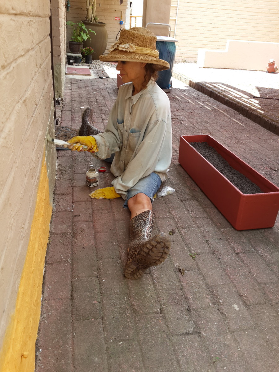 Charmaine, age 62, painting the wall. Every opportunity is used to get some exercise - in this case doing the splits! Sedgefield, South Africa.