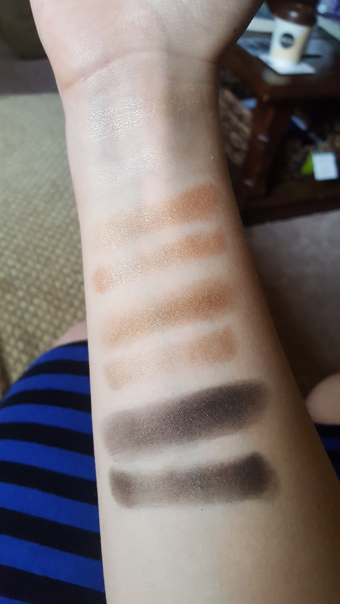 Finger and brush swatches of the left column of shadows from the Wet N Wild Comfort Zone palette, starting with the pale shimmery yellow, which is a bit hard to see on my skin