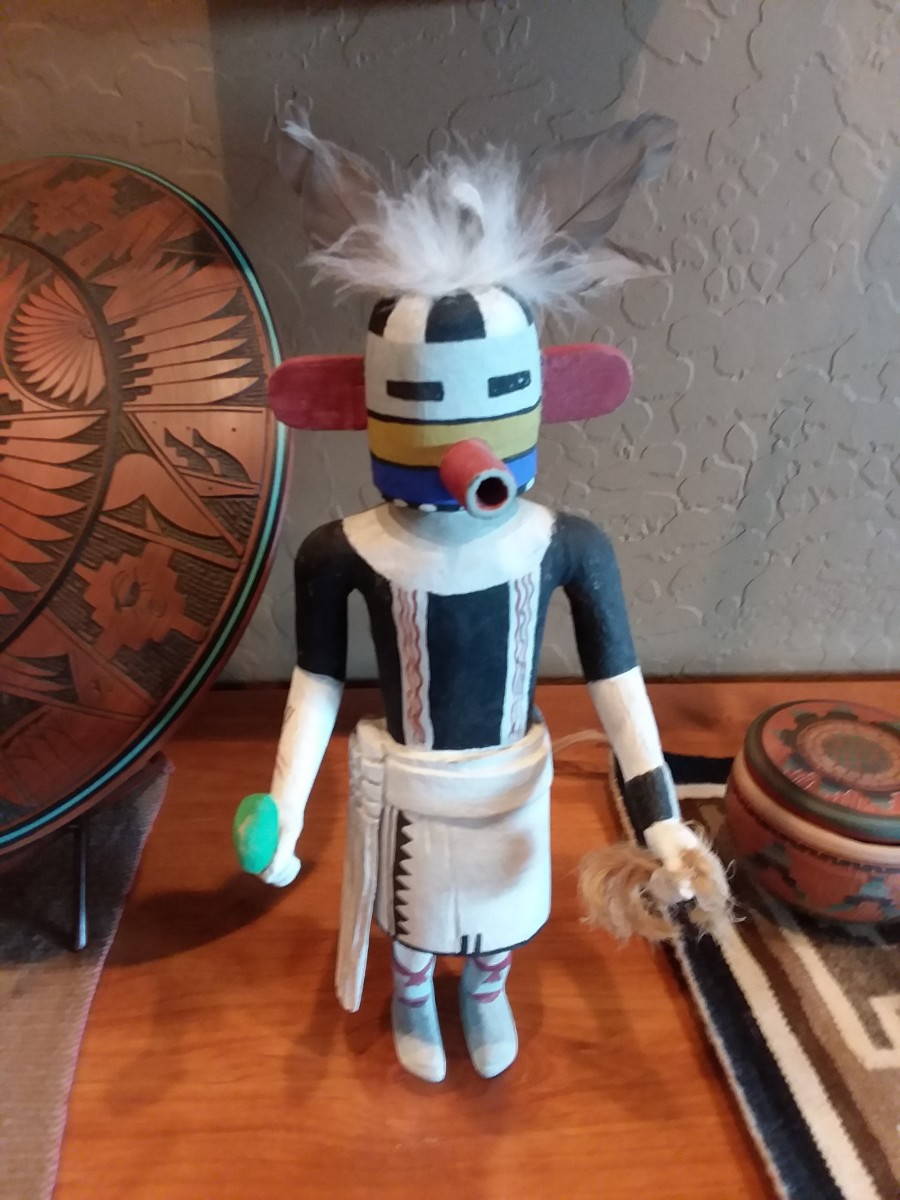 Notice that this Kachina does not have a base, which means that there isn't an artist's signature at the bottom. Really old Kachinas did not have a base, but the feathers appear new.  Unsure of origin.
