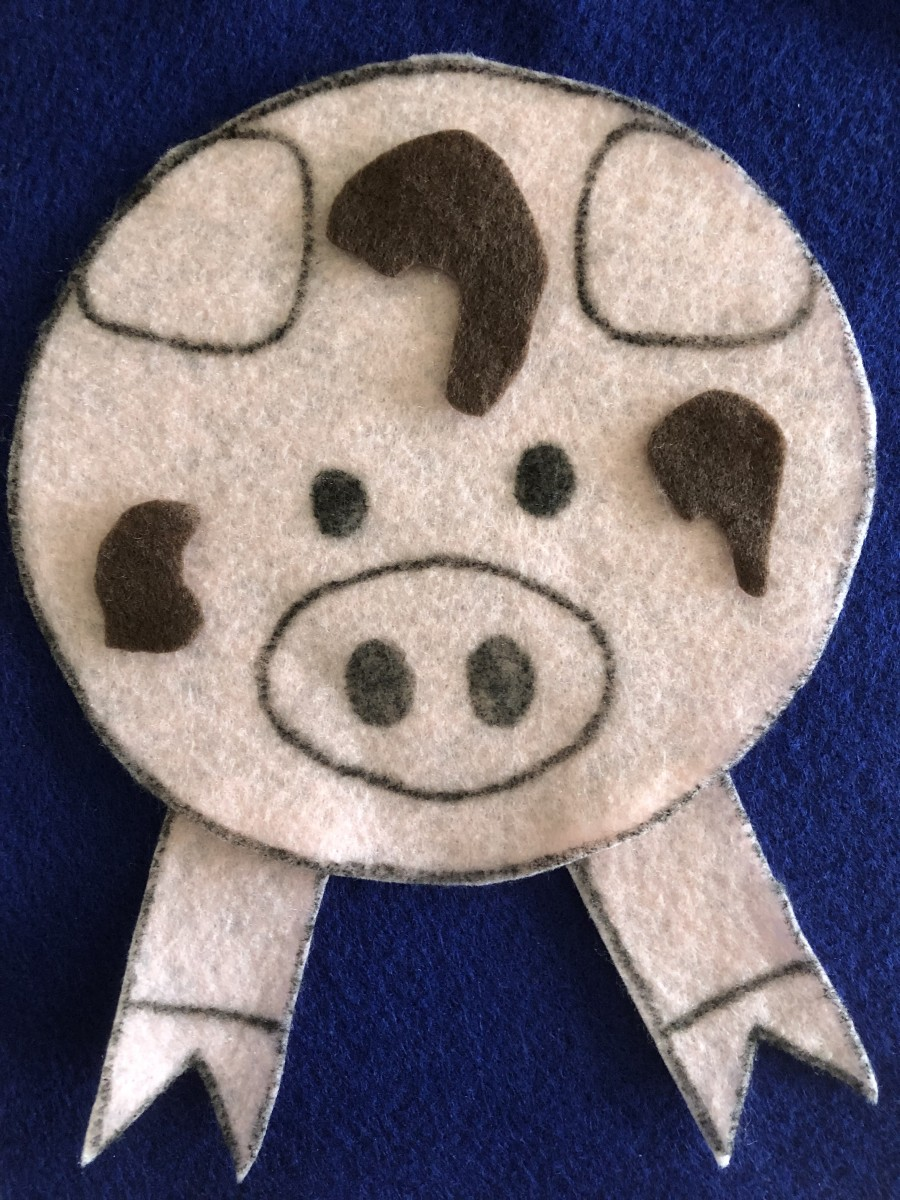 Cut out another face for the other side of the pig, and cut mud splotches from brown felt. Flip over to this side when you get to the part in the rhyme when they jump in the mud.