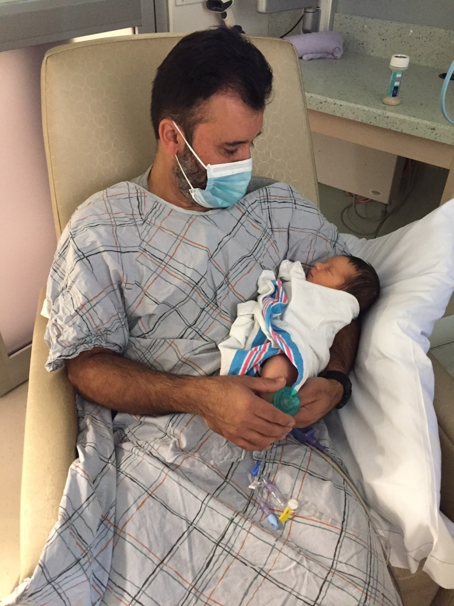 This is a picture of my dad visiting our little guy in the NICU. The NICU had specific rules for visitors and we only allowed our parents to visit the baby while he was in there.  **Notice the face mask and scrubs- they were mandatory during visits.