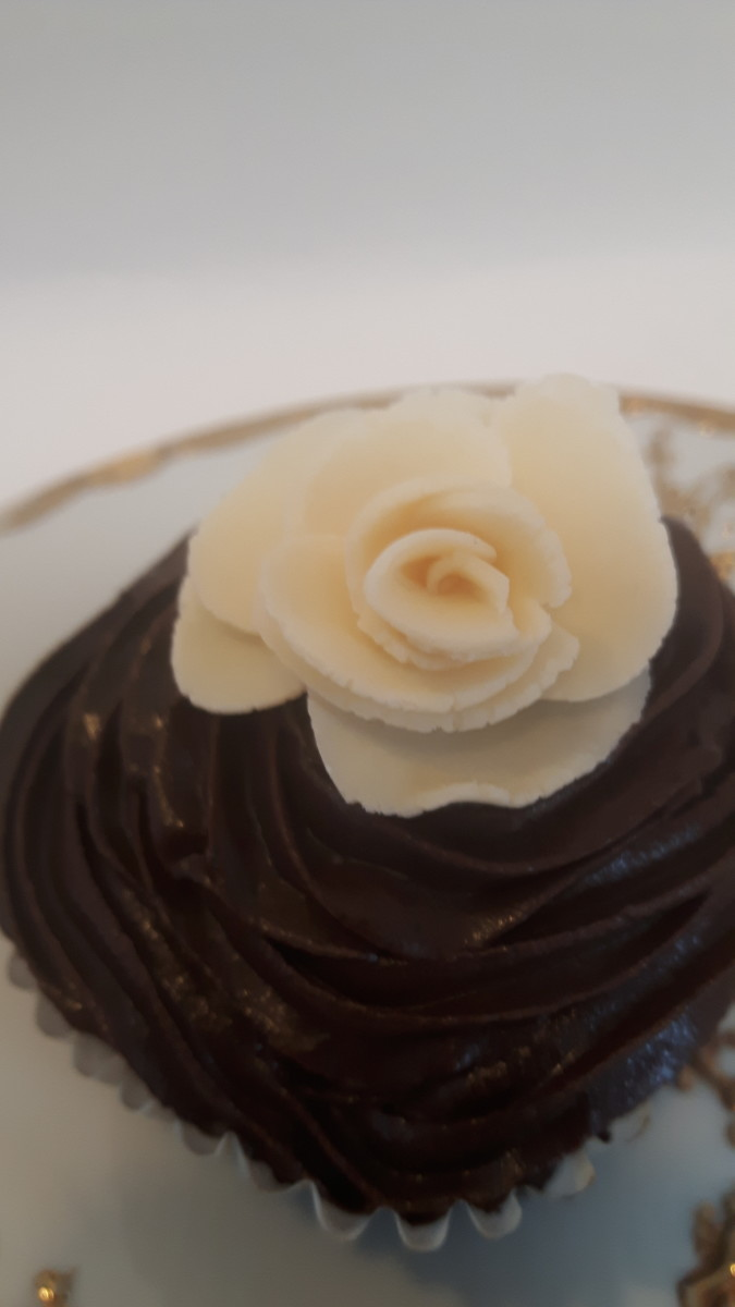 White modeling chocolate rose on a plastic bag chocolate cupcake
