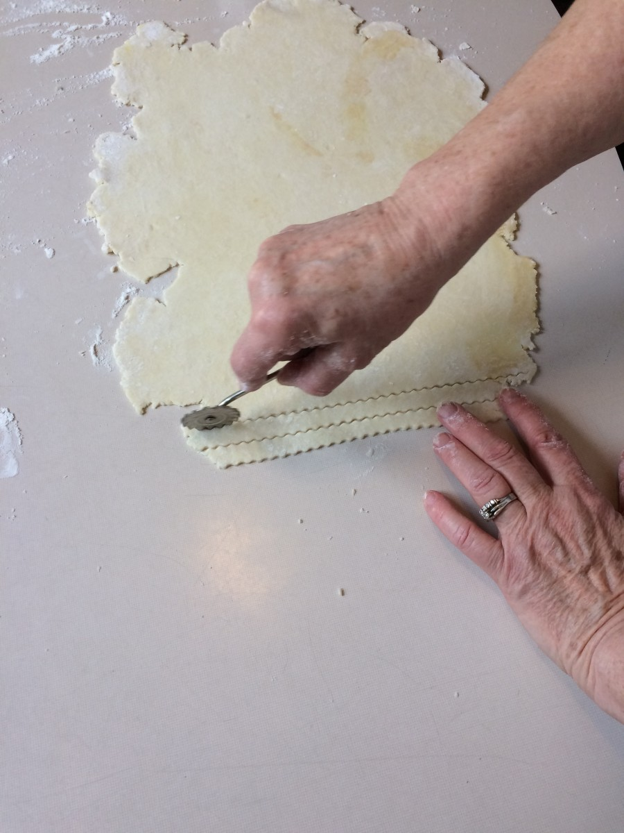 Begin by slicing off the jagged edge of the dough and discarding that back to the bowl for future use. Now you have a beginning edge that you can follow for the rest of your cuts.