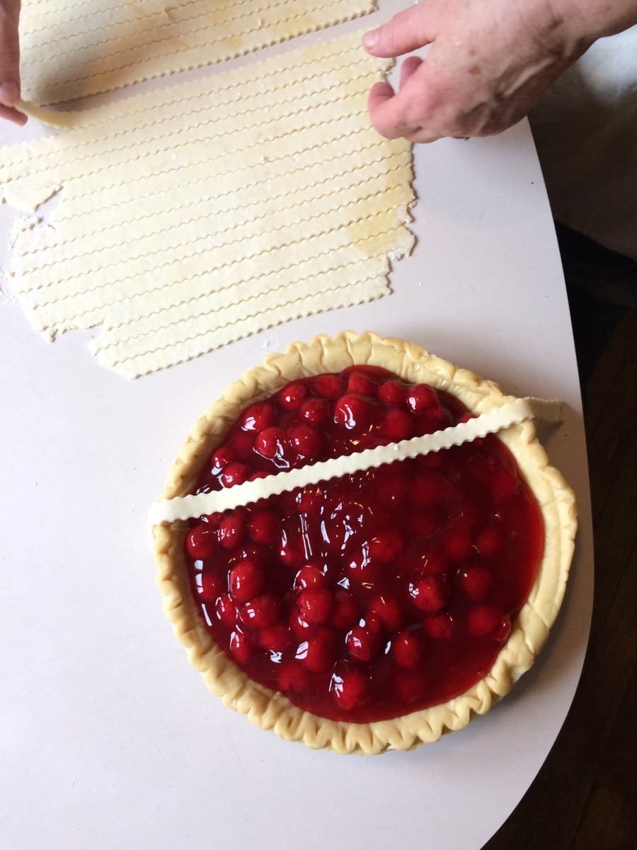Lay the first strip directly across the pie, close to the center.