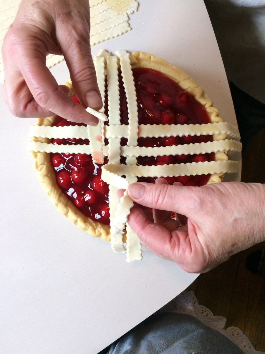 Here, I am showing how I weave the strips by lifting up ones that are already laid on the pie filling. This means that I need to be very careful and not get too much filling on my fingers or the strips.
