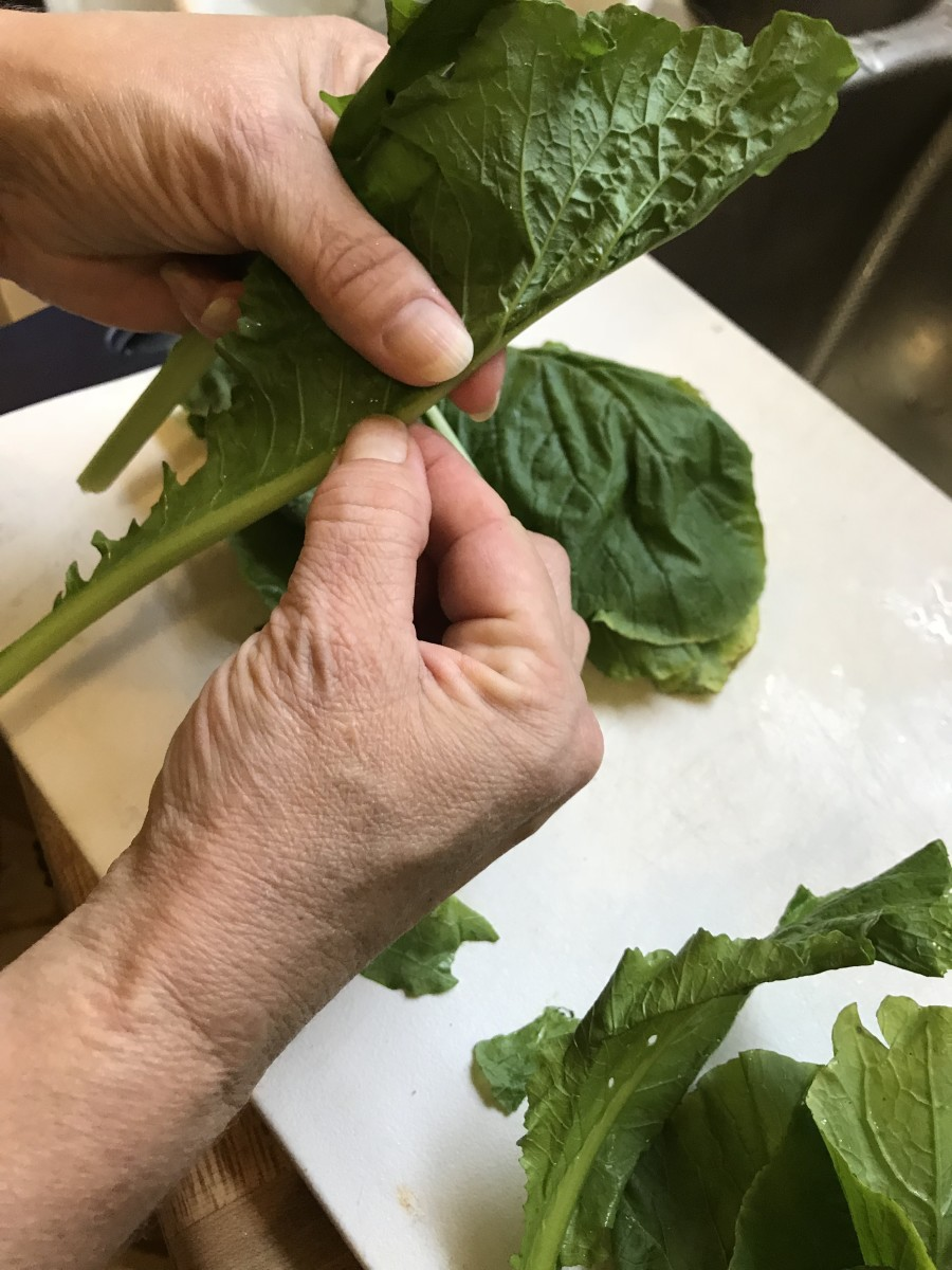 Fold the greens in half with the rib to the outside. Grasp the rib and pull back. This removes the majority of the stringy, woody part. Then stack the leaves about 5-6 deep.