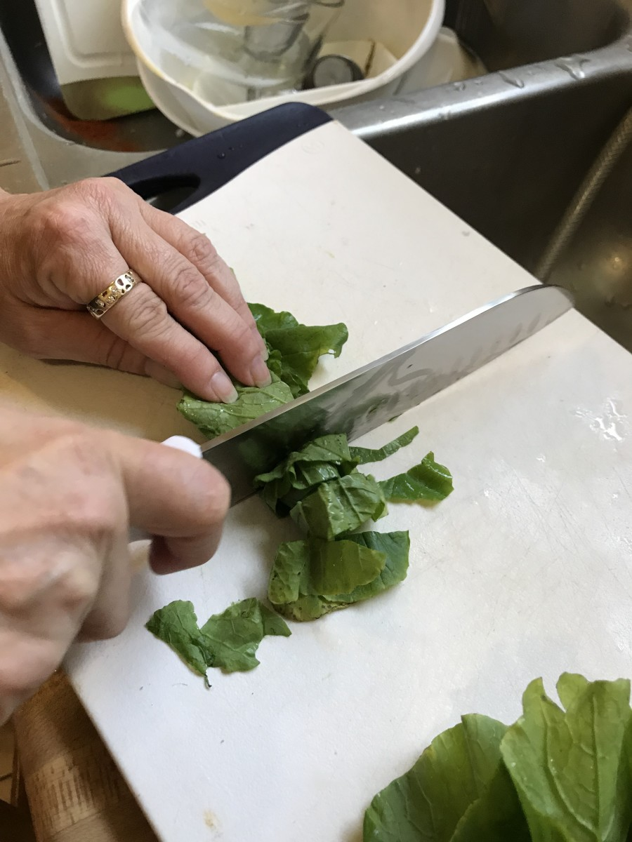 Once rolled, cut each stack of leaves into ribbons by slicing the roll into about 1/2 inch slices. You can also simply tear the leaves into small pieces, but I think this is just as fast and makes a nice, consistent finished dish.