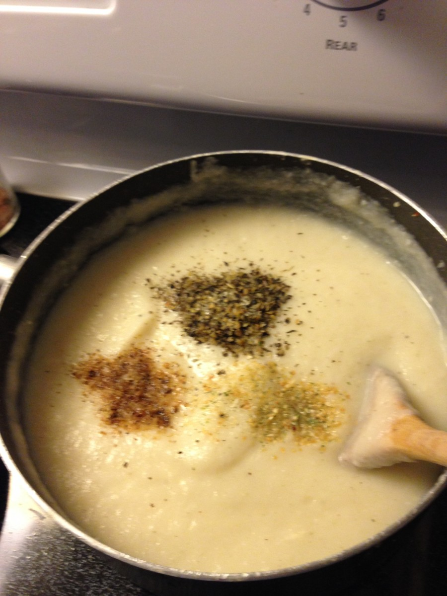 Cauliflower Alfredo simmering gently on the stove as seasonings are added.