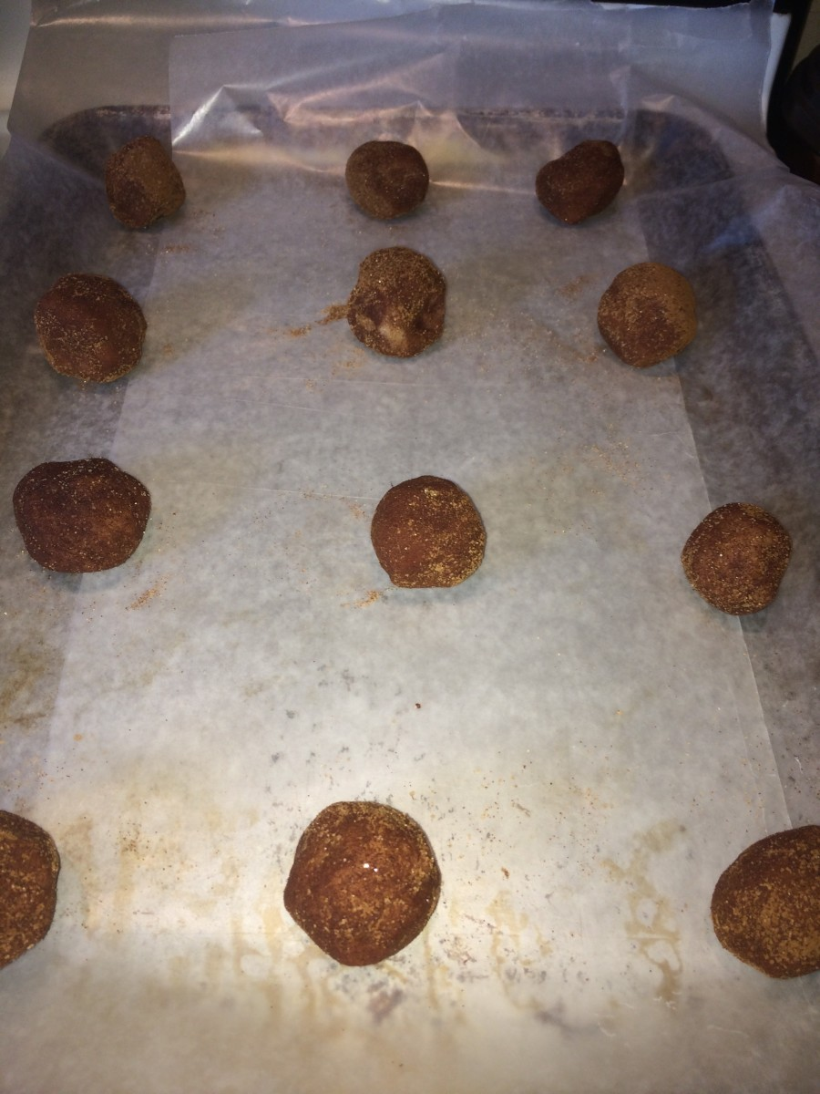 Place cookie dough balls on an ungreased cookie sheet 2 inches apart. Using baking sheets or pan lining paper is fine. Be sure not to grease the pan otherwise the underside will likely burn.