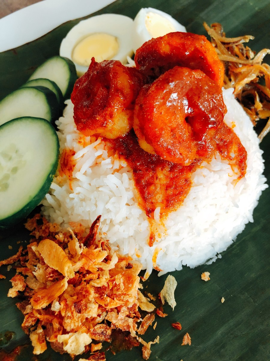 Nasi Lemak. There are a variety of side dishes served on top of the nasi lemak: fried anchovies, sambal udang, fried fish, hard-boiled egg, and fresh sliced cucumber.