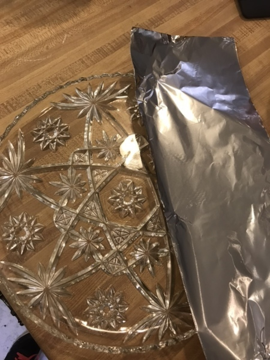 Prepare a cake plate by placing strips of foil along the edges, making sure to leave the center of the plate uncovered. Place a dollop of frosting in the center of the plate.