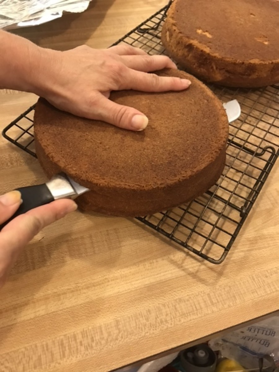 With a serrated knife, cut each cake in half horizontally. Separate the cut halves and set one aside. Just try to keep the knife as even as possible, but don't worry too much about it.
