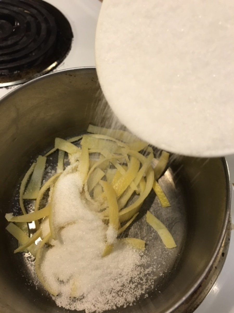 After the lemon peel is drained the third time, you're ready to begin the candying process. Return the lemon zest to the saucepan. Make a simple syrup of one cup white sugar and one cup cold water.