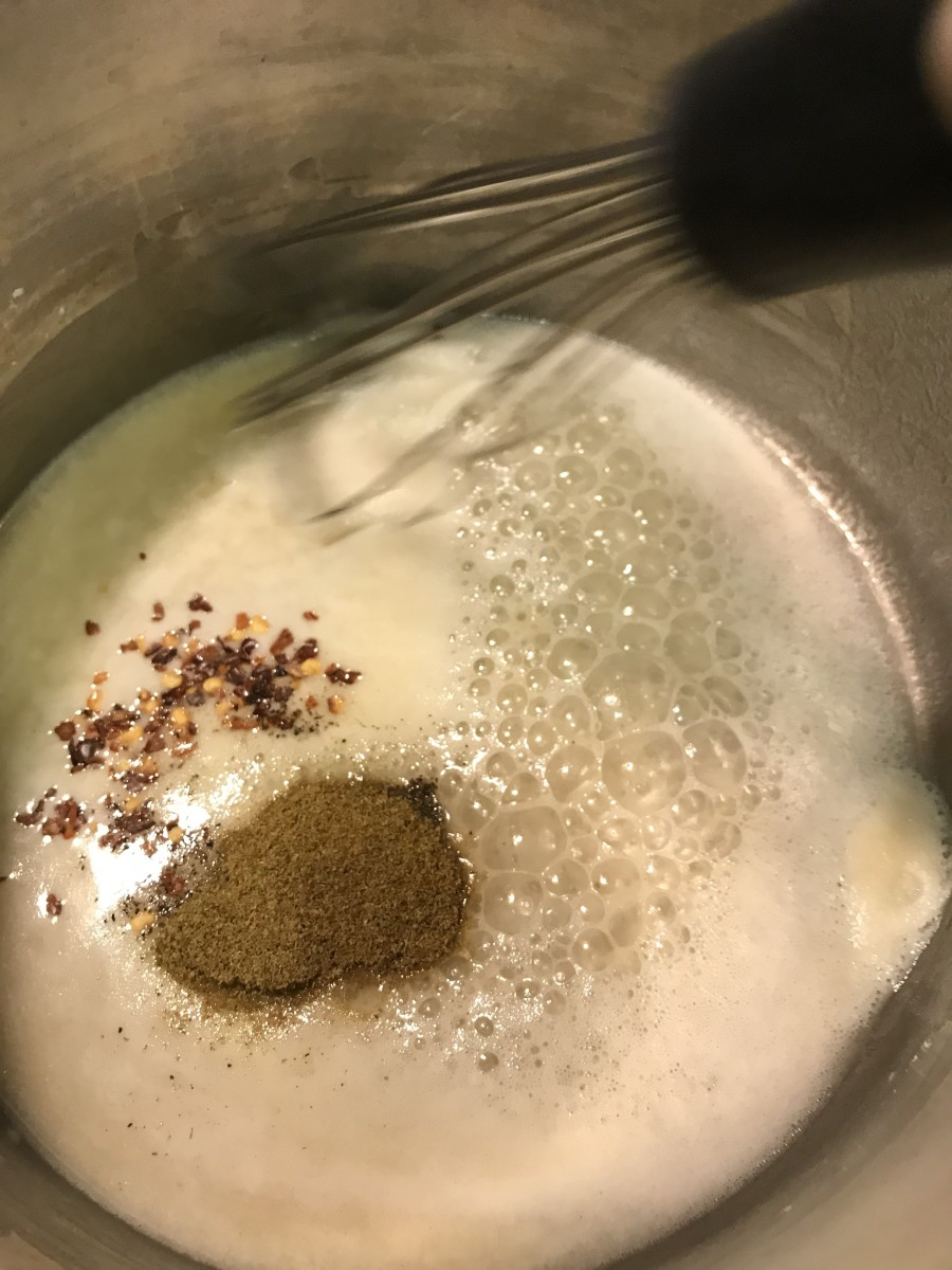 Add red pepper flakes, black pepper and cumin to the hot oil and flour mixture, and whisk to combine. This helps release more of the flavor of the pepper and cumin.