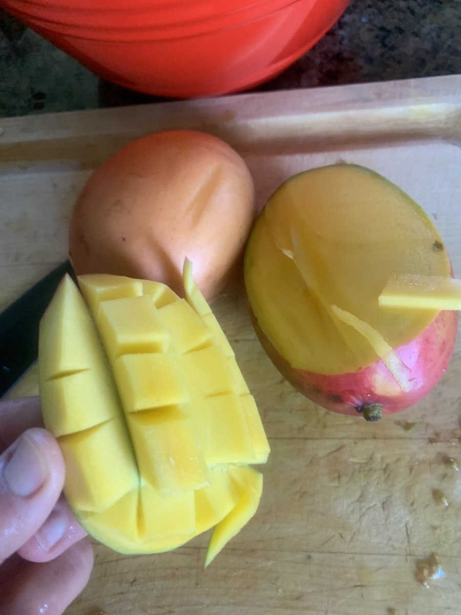 To easily dice mango, slice along the large pit. Score the fruit and turn skin inside out. Remove pieces.