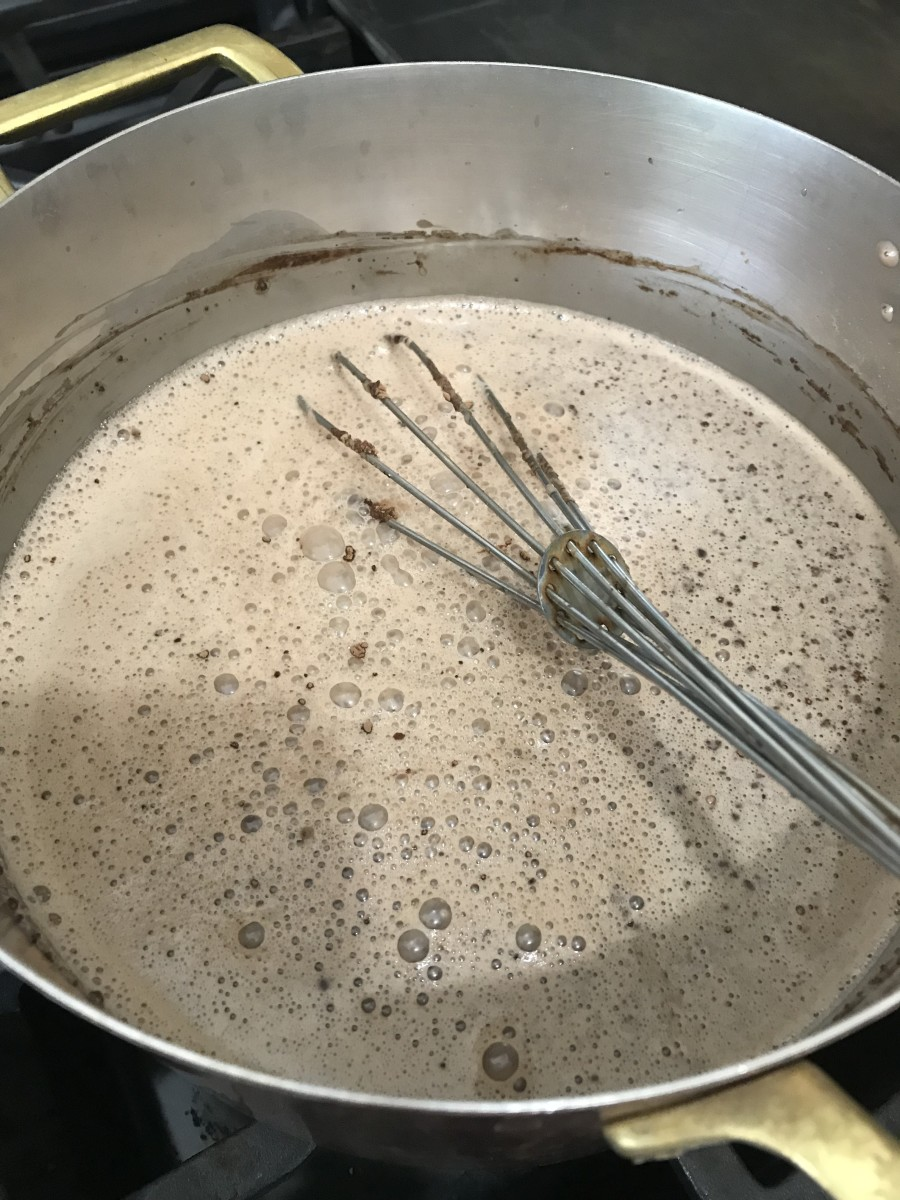 Combine the sugar, half and half, milk and cocoa in a saucepan over medium heat. Bring up to a bare simmer, whisking well to fully combine. Don't let it actually boil - a mere simmer is perfect.