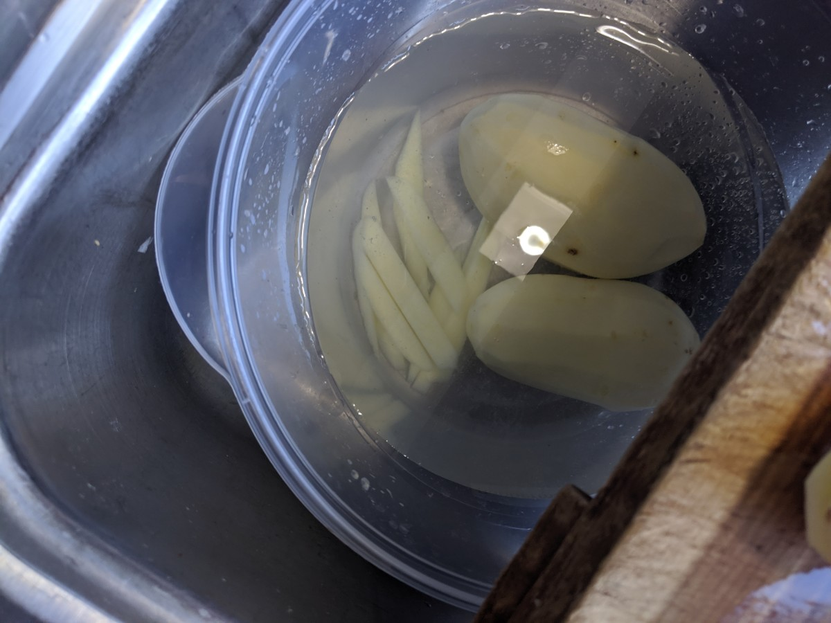 Place the cut fries in salt water and cut the remaining potatoes.