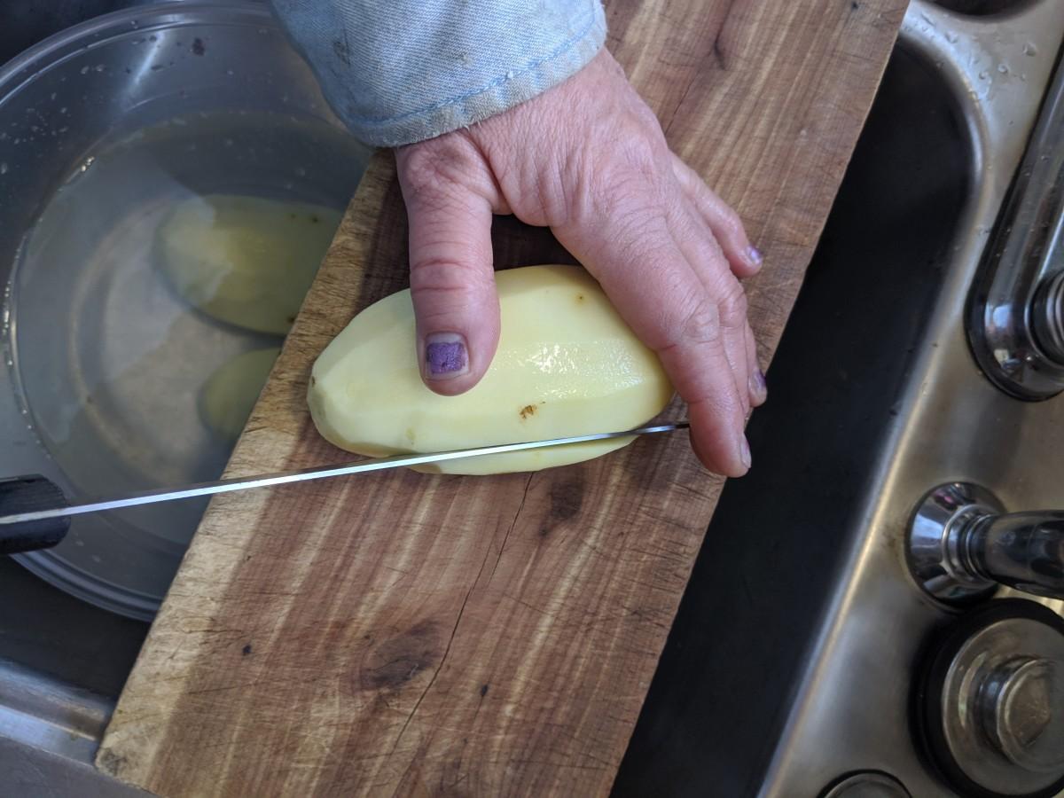Slice downward through the potato.