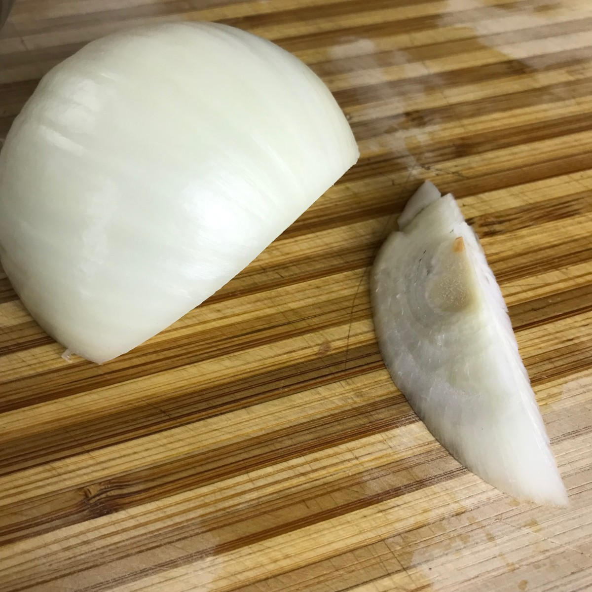 Trim the ends of the onions, split them in half, and remove the outer layer. If you have any root ends left on like the one in the photo, be sure to trim them out at a diagonal. If they are left intact, the onion layers will not separate properly.