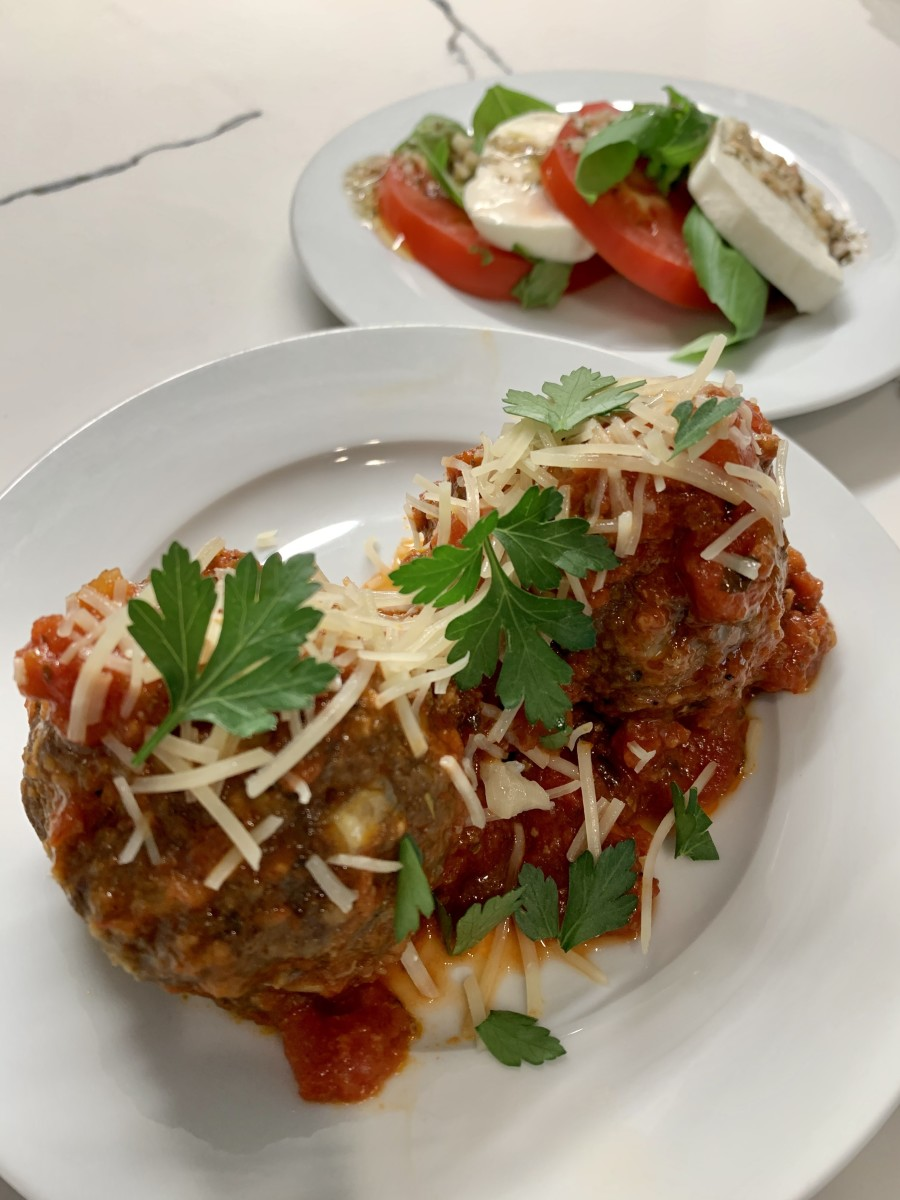 Italian meatballs garnished with Parmesan and parsley, with caprese salad on the side