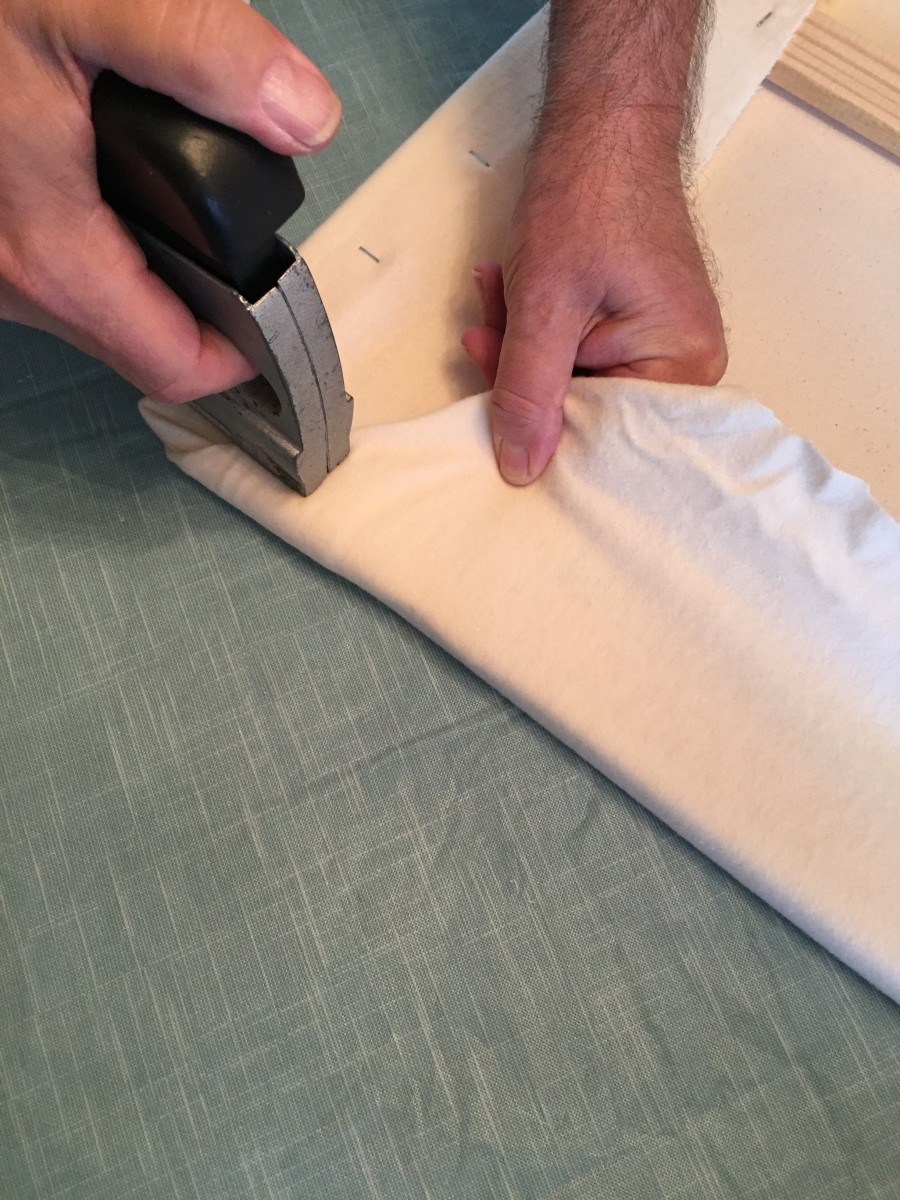 Step 4- It's important to pull the flannel tight as you go along with the staple gun, this way your fabric will be nice and smooth on the other side of the board and your felt pieces will stick without effort.
