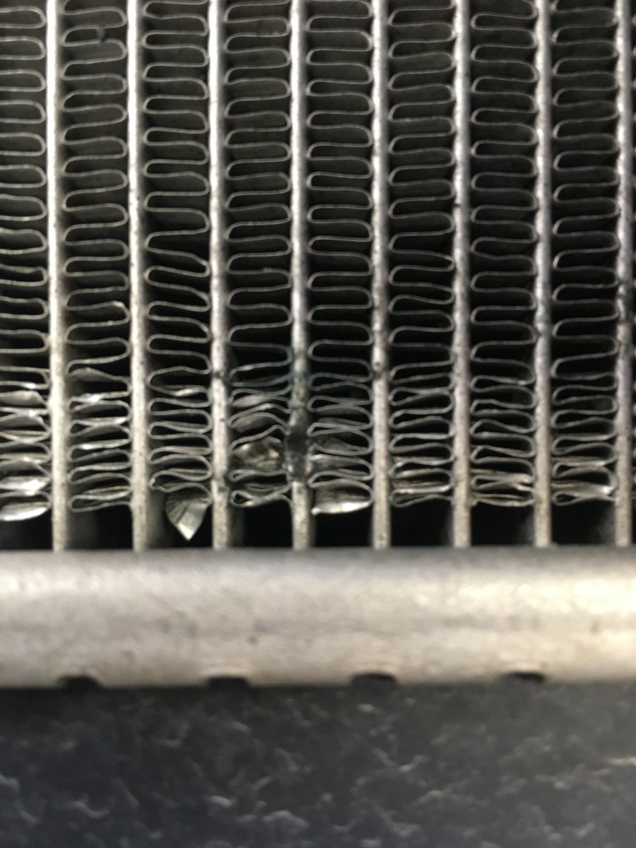 Rock damage to an AC condenser