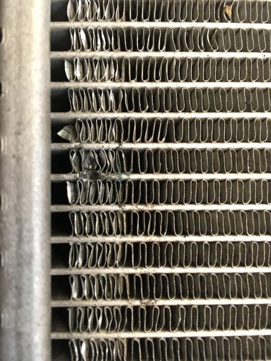 Rock damage to an AC condenser. Each horizontal line is a small tube which carries freon, and the the vertical loops that look like corrugated cardboard are the cooling fins that cool the freon.