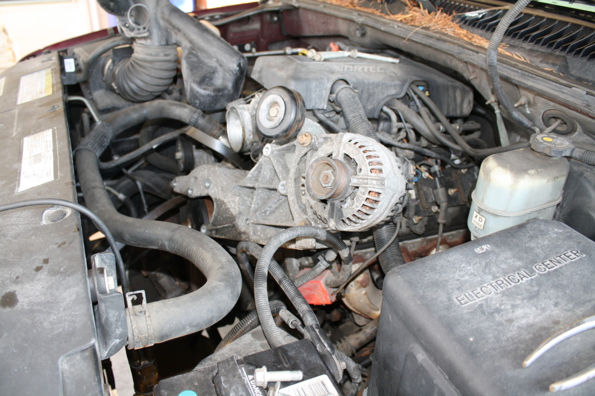 Set the bracket out of the way. Don't stress the alternator cables.