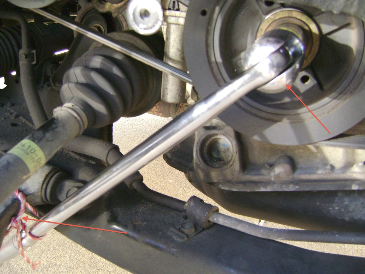 D. To loosen the crankshaft pulley bolt, secure the 22 mm socket to the bolt (upper right) and brace the breaker bar against the lower control arm (lower left).