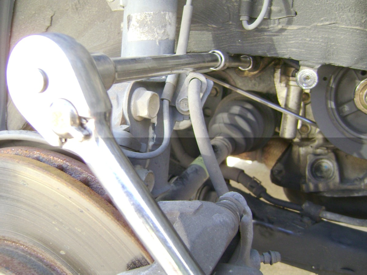 "L.  Loosen and remove the power steering pump adjustment bolt, with a socket wrench attached to a ½"" extension."