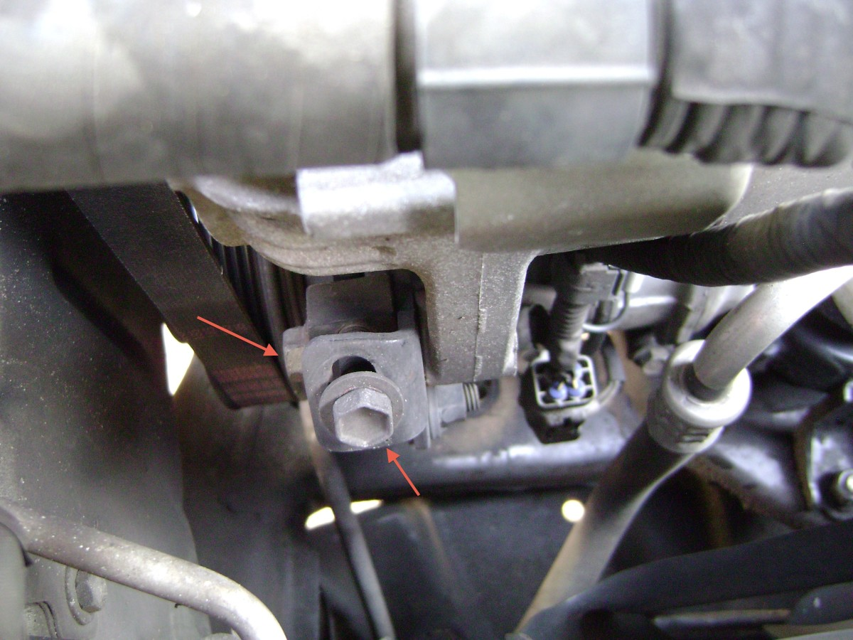 J. Loosen the alternator locking bolt (left), then turn the alternator belt adjustment bolt (right) counter-clockwise to relieve tension on the belt.