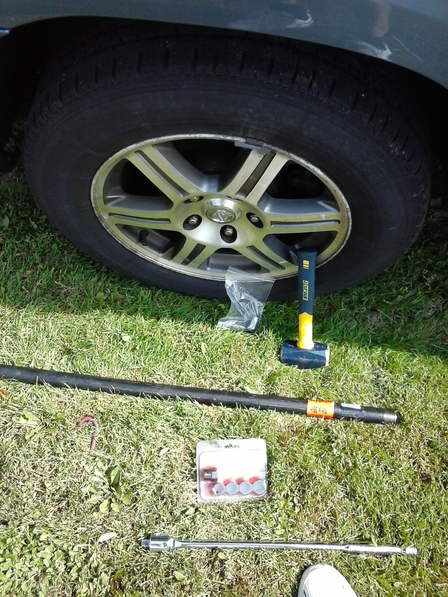"3 lb. hammer, 1/2"" drive breaker bar, 1/2"" drive with hex head nut extractor sockets, 1""x36"" iron pipe, and new lug nut."