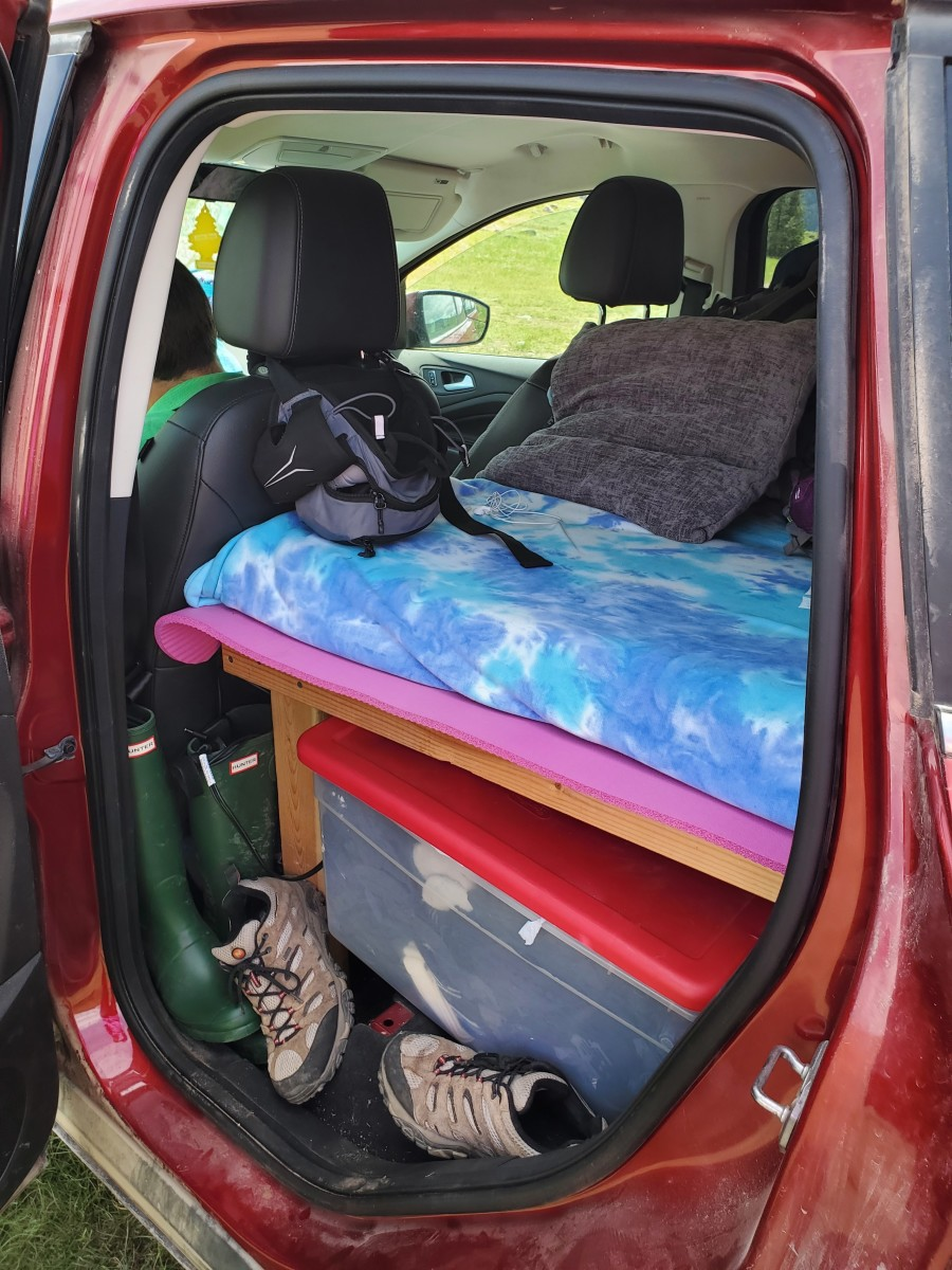 Customize your car bed to fit in your car, and make it high enough to provide extra storage underneath. We use storage bins to keep our belongings organized.