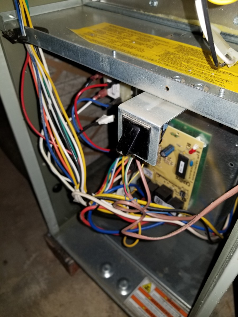 You can see the small red bulb that indicates many different series of blinking lights that can mean multiple different errors. The black button above activates the furnace when it is pressed in by the metal doors.