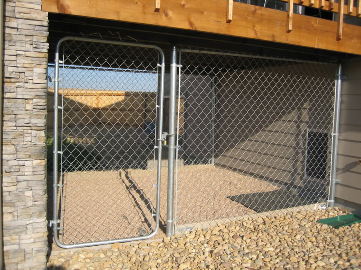 Outdoor dog run with stone kennel flooring.