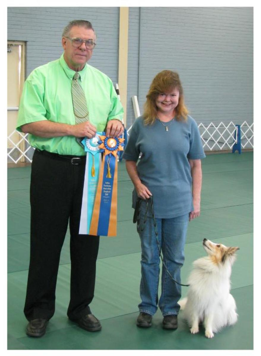 "Jericho, the judge and his owner with his ""High in Trial"" and ""High in Trial Other Breed"" ribbons won at an ASCA obedience trial. Notice Jericho's strict attention to his handler.  He's watching for more commands!!!"