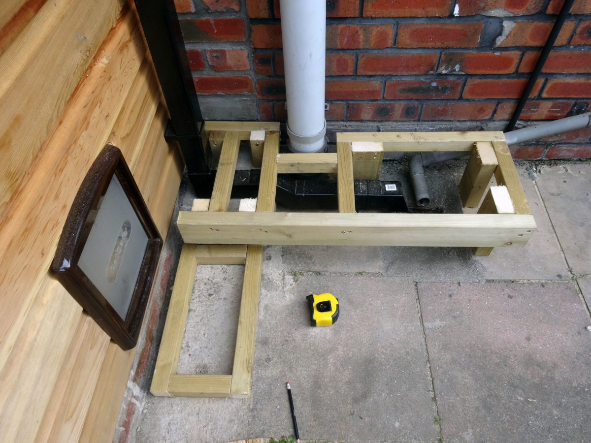 Two of the support posts for the plant potter frame also supports one side of the cat's step.