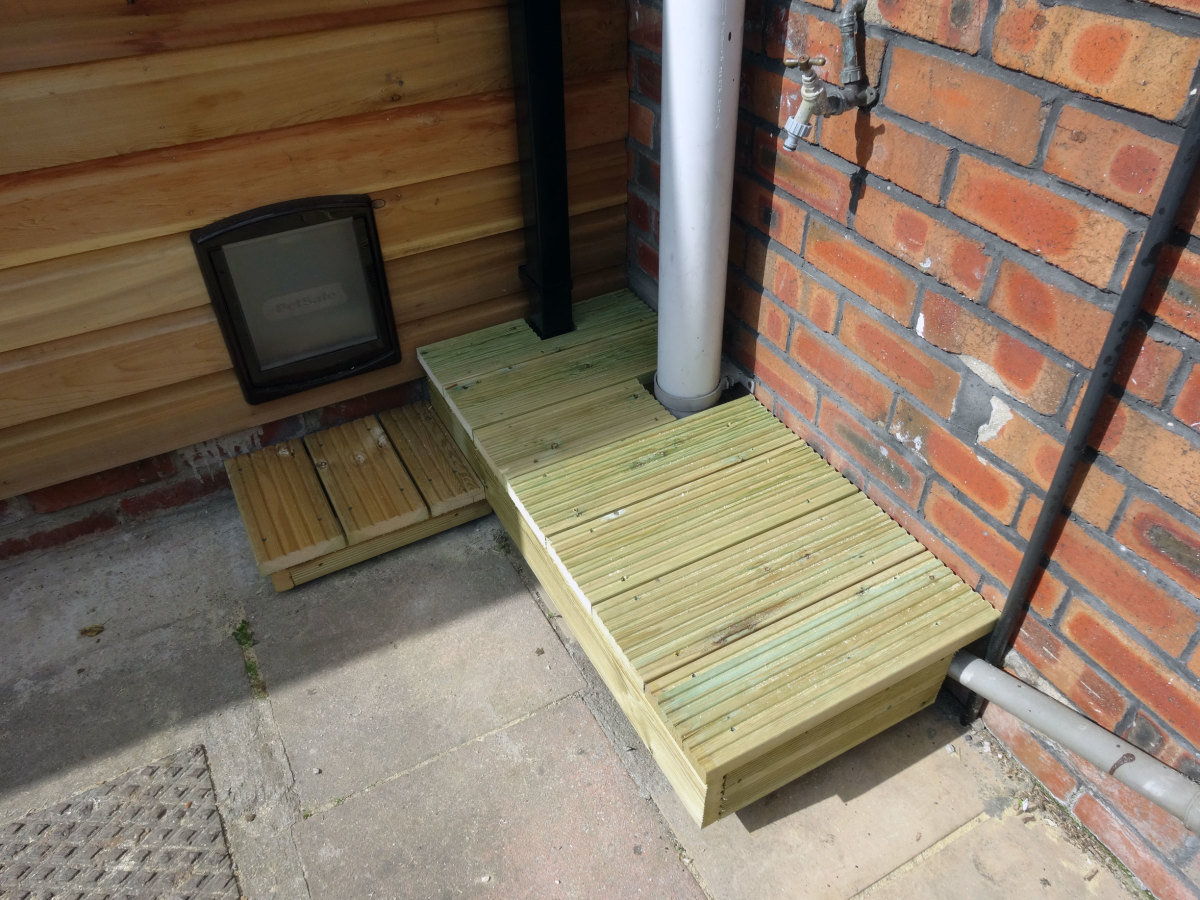 Decking fitted to base, last peice locking platform in place around the rain water down pipe.