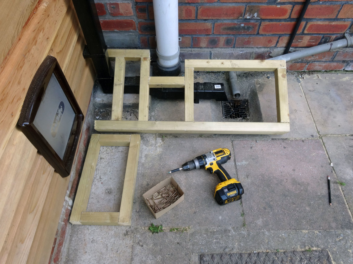 Decking frame designed to fit around soil waste and rain water down pipe.