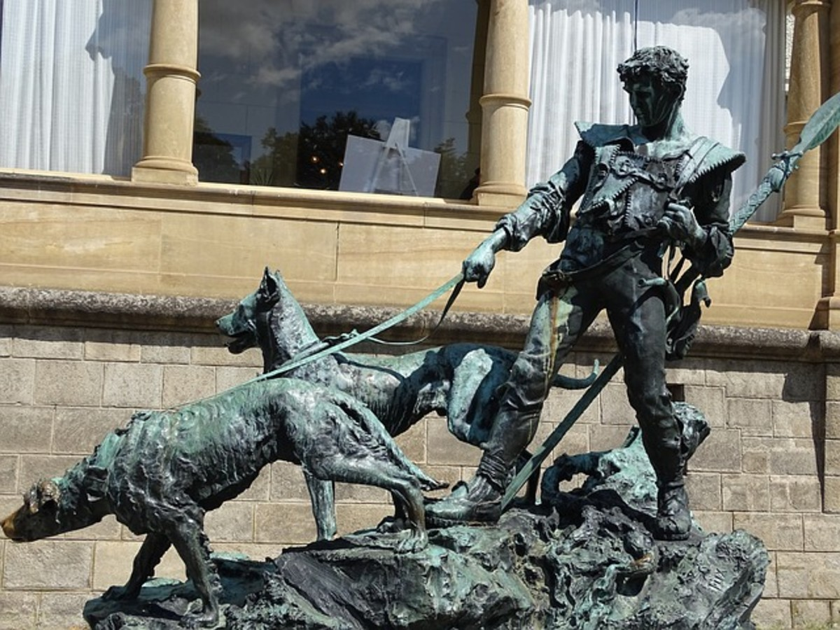 Statue of man holding dogs
